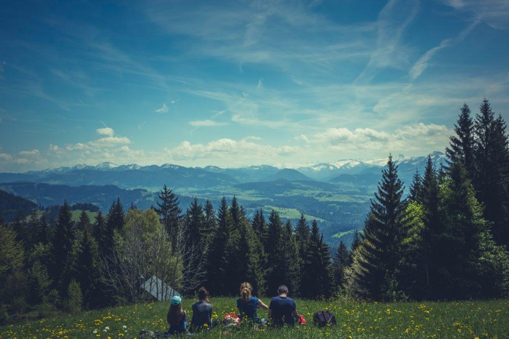 Rodzina siedząca napolanie patrzy wstronę gór.